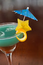 Blue hawaiian cocktail served on a busy bar top garnished with a carambola slice and an umbrella Royalty Free Stock Photo