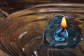 Blue heart shaped candle floating on water, festival concept Royalty Free Stock Photo