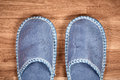 Blue home slippers on a brown wooden floor Royalty Free Stock Photo