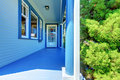 Blue house covered front porch with entrance door. Stock Photo