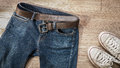 Blue jeans with leather belt and dirty white sneaker shoes  on t Royalty Free Stock Photo