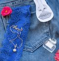 on blue jeans lie a perfume bottle, a gold filigree work clock, Royalty Free Stock Photo
