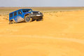 Blue Jeep Wrangler Rubicon Unlimited at desert sand dunes Royalty Free Stock Photo