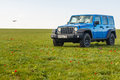 Blue Jeep Wrangler Rubicon Unlimited in wild tulip field near saltwater reservoir lake Manych-Gudilo Royalty Free Stock Photo