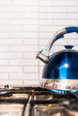 Blue kettle teapot stands on a gas cooker Royalty Free Stock Photos