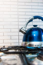 Blue kettle teapot stands on a gas cooker Royalty Free Stock Image