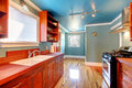 Blue kitchen with cherry cabinets and shiny floor. Royalty Free Stock Image