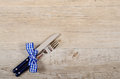 Blue knife and fork with checkered bow on a wooden table diner Royalty Free Stock Photos