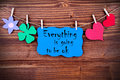 Blue label with life quote everything is going to be ok tag or hearts and flower and four leaf clover on a line on wooden Royalty Free Stock Photography