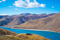 Blue lake and mountain ranges yamdrok with sky in tibet china Royalty Free Stock Photos