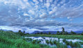 Blue Landscape with Dramatic Clouds Mountain and Water Royalty Free Stock Photo