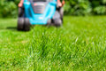 Blue lawn mower on green grass cut the grass Royalty Free Stock Photo