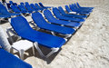 Blue lounge chairs rows of several on the beach Stock Photography