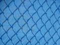 Blue mesh fencing with shadows Royalty Free Stock Photo