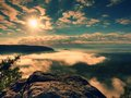 Blue misty daybreak. Sandstone cliff above deep foggy valley in mountains. Royalty Free Stock Photo