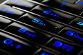 Blue mobile keypad under dark Royalty Free Stock Images