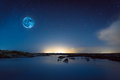 Blue moon a hanging in the sky above the lagoon iceland on a starry night Royalty Free Stock Photos