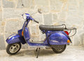 Blue motorcycle on a stoned street motor scooter vespa with stone wall in background Stock Photos