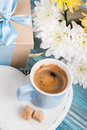 Blue mug of black coffee with a bouquet white chrysanthemum and gift valentines day or birthday concept Stock Photo