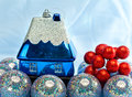 Blue new year s ball and toy small house new year s still life on a blue background Royalty Free Stock Photos