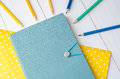 Blue notebook with colour pencils on yellow paper Royalty Free Stock Photo