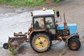 Blue old and rusty tractor running after rain storms