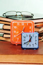 Blue and orange alarm clocks a pile of old books and glasses on the table Royalty Free Stock Image