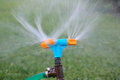 Blue and orange sprinkler watering grass. Garden irrigation system watering lawn. Closeup image of a garden sprinkler on Royalty Free Stock Photo