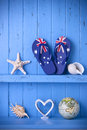 Blue painted rustic wood background australian flag thongs starfish shells globe love heart Stock Photography