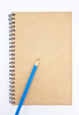 Blue pencil on brown notebook s cover white background Royalty Free Stock Images