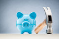 Blue piggy bank and a hammer front view of with next to it Royalty Free Stock Photo