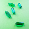Blue pills on green background still life Royalty Free Stock Image