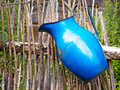 Blue pitcher large hanging on a wooden rural fence once good for milk or wather Royalty Free Stock Images