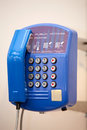 Blue public phone a on a wall Royalty Free Stock Photos