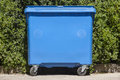 Blue recycling container for paper with green bush background