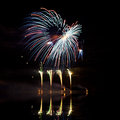 Blue red and green fireworks reflected in a murky lake Royalty Free Stock Images