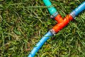 Blue, Red Plastic Water Pipe Splitter on Green Grass Royalty Free Stock Photo