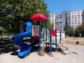 The blue red white children s slide in a city park on a background of multi storey buildings and a sky in sun Royalty Free Stock Photos