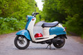 Blue retro scooter in the forest with helmet Royalty Free Stock Photo