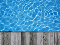 Blue ripped water in swimming pool with wood flooring background for display picture or object Royalty Free Stock Images