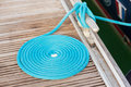 Blue rope coiled on a wooden dock and tied to metal cleat Royalty Free Stock Images