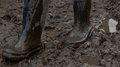 Blue rubber boots covered in dirt gait on the mud ukraine Royalty Free Stock Photography