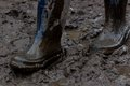 Blue rubber boots covered in dirt gait on the mud ukraine Royalty Free Stock Image