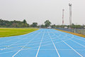 Blue running track in sport stadium Stock Photography