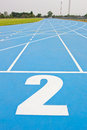 Blue running track in sport stadium Stock Images