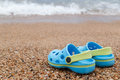 Blue sandals slipper on the sand pair of slippers crocs Stock Images