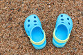 Blue sandals slippers on the sand pair of crocs Royalty Free Stock Photo