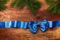 Blue satin ribbon with bow and fir branches on wooden boards Stock Image