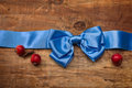 Blue satin ribbon with bow and red apples on wooden boards Royalty Free Stock Photography