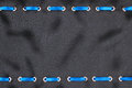 Blue satin ribbon inserted in the gold rings on black silk trendy background Royalty Free Stock Image